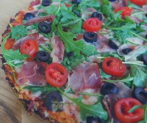 Niskowęglowodanowa pizza na spodzie z kalafiora z pomidorkami, rukolą i szynką parmeńską